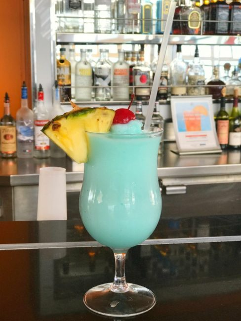 Colorful St. Patrick's Day Drink that features a green color with cherries and pineapple toppings