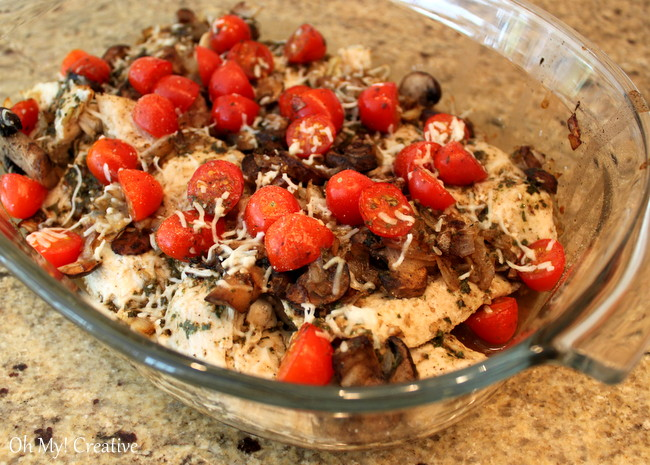 Chicken in a bowl with tomatoes, cheese, and mushrooms