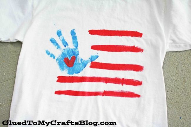 Flag made with a white shirt, red paint and handprint in blue