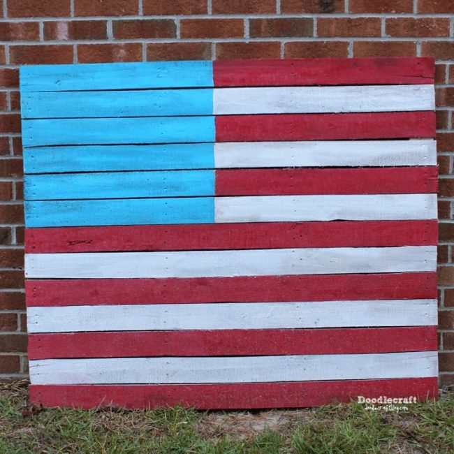 Wooden pallet painted with red and white stripes and blue square