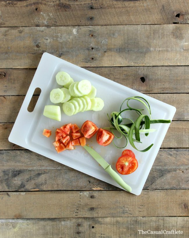 Sliced cucumbers, diced tomatoes, and cucumber peel on a white cutting board.