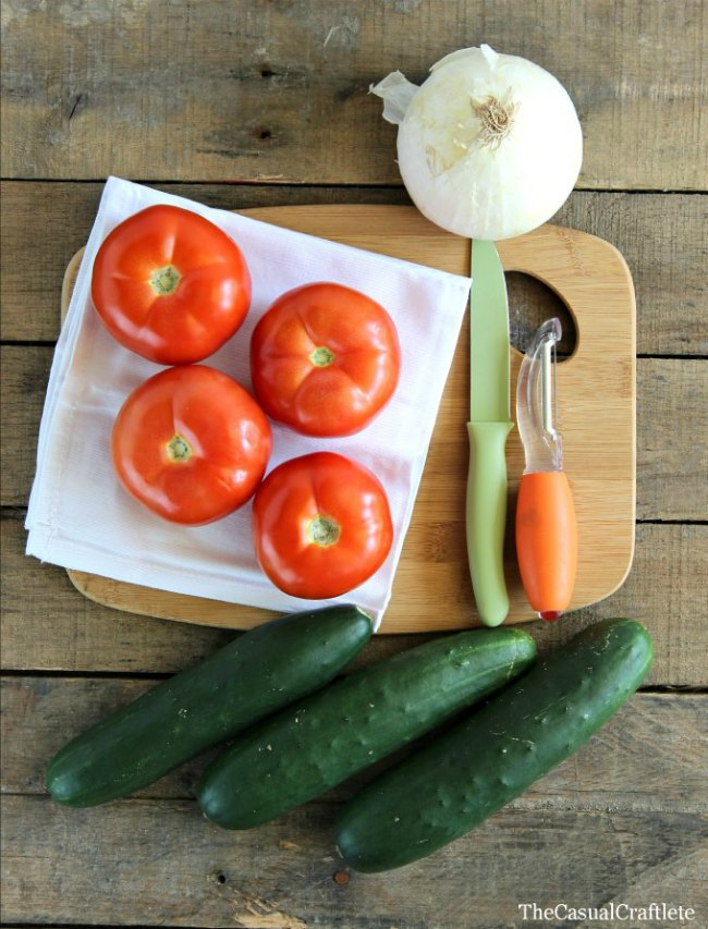 Whole cucumbers, 4 tomatoes, and a white onion on cutting board with a small knife and vegetable peeler.