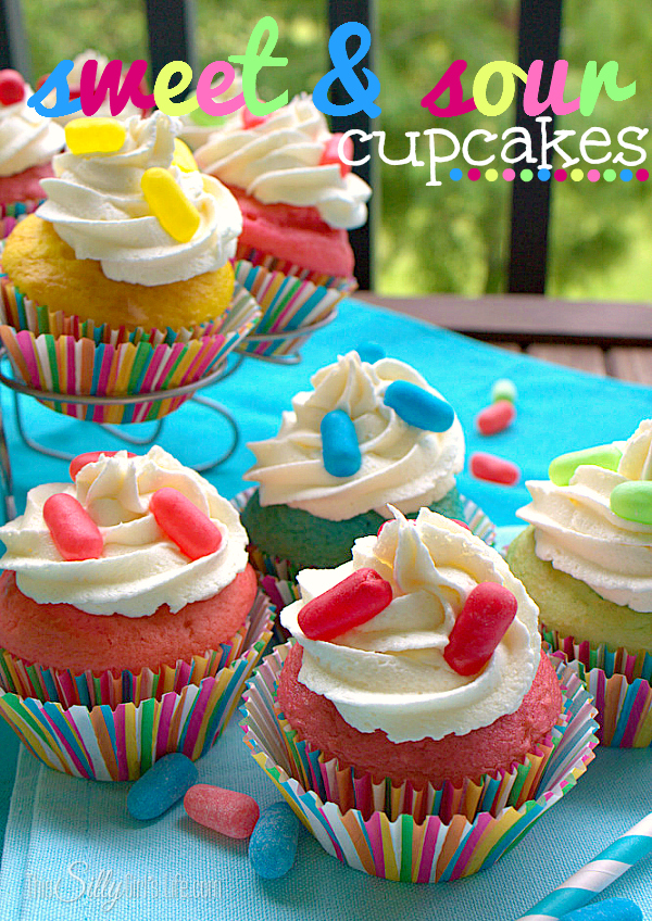 yellow and red cupcakes topped with white frosting and sour pastel candy on top