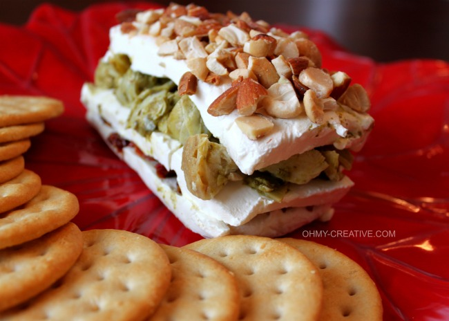 This Layered Sun-dried Tomato and Artichoke Appetizer is easy to make, tasty and perfect for any occasion. The red and green layers make it especially pretty for the holidays!  |  OHMY-CREATIVE.COM
