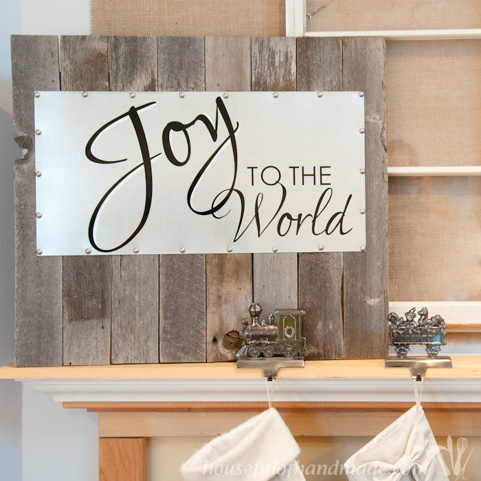 Create the perfect Farmhouse Christmas decor with some reclaimed wood and a piece of sheet metal. You can change up the saying on the metal for any season. | Housefulofhandmade.com