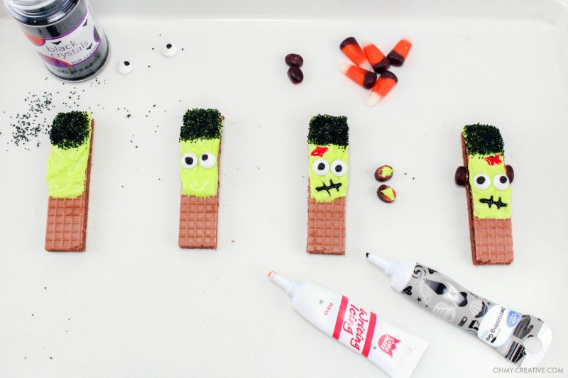 Adding eyes and mouth and using sprinkles for hair to create Frankenstein Cookies