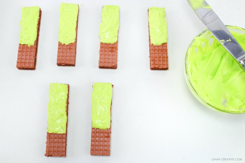 Spreading green icing on half the wafer cookies for the Frankenstein Cookies using a knife