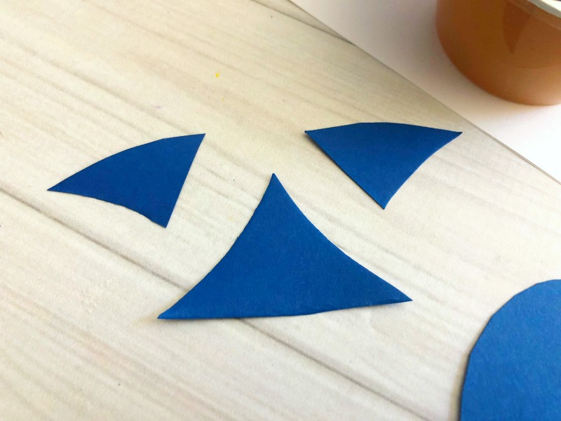 Cut out fins for the sharks out of blue paper.
