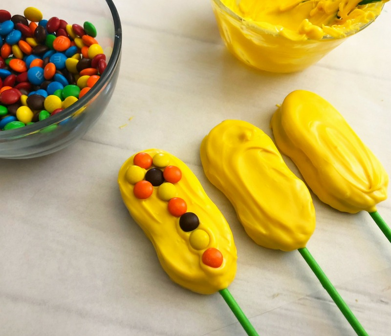 Assembling dipped nutter butters to create Indian Corn Harvest Cookies. Harvest Indian Corn Cookies are a perfect treat to serve at any fall celebration or Thanksgiving! OHMY-CREATIVE.COM | Fall Cookies | Indian Corn | Fall Desserts | Cookie Pops | Nutter Butter Cookies | #indiancorn #indiancorncookies #falldessets #fallcookies #harvestcookies