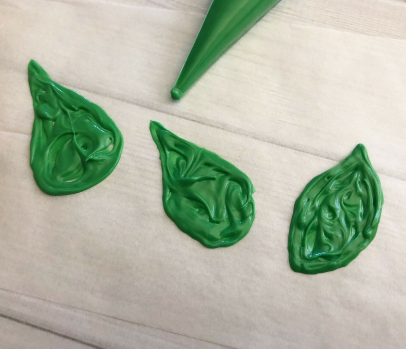 Green candy melt leaves for Indian Corn harvest cookies. Harvest Indian Corn Cookies are a perfect treat to serve at any fall celebration or Thanksgiving! OHMY-CREATIVE.COM | Fall Cookies | Indian Corn | Fall Desserts | Cookie Pops | Nutter Butter Cookies | #indiancorn #indiancorncookies #falldessets #fallcookies #harvestcookies
