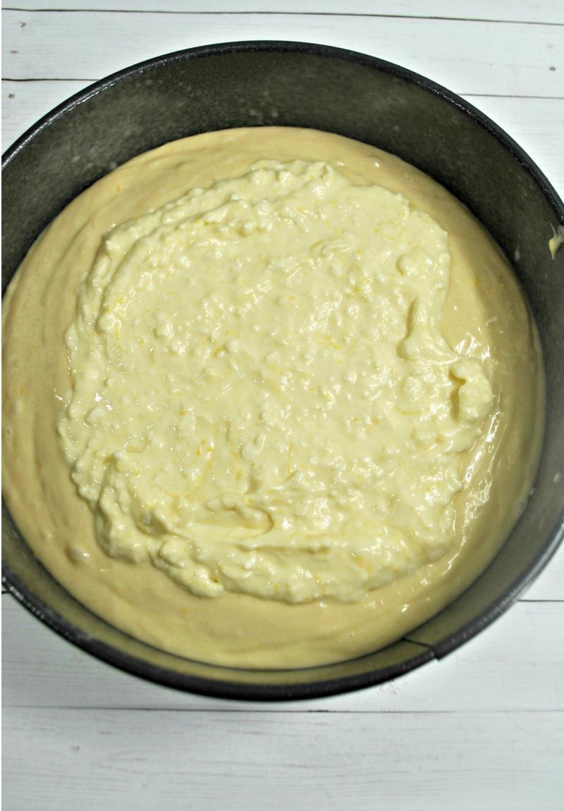Layering cream cheese filling on blueberry lemon crumb cake recipe