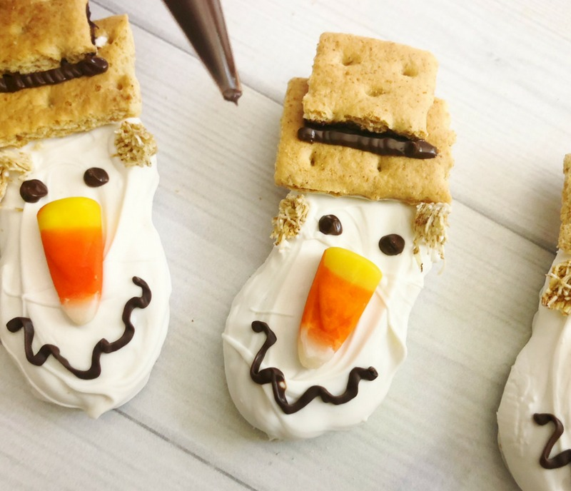 Use melted chocolate candy to create the mouth, eyes and hat for your scarecrow cookies Check out our Cute Scarecrow Nutter Butter Fall Cookies for your harvest fest or Thanksgiving dessert buffet table! #Scarecrow #Scarecrowdessert #fallcookie #falldessert #thanksgivingdessert #nutterbutter