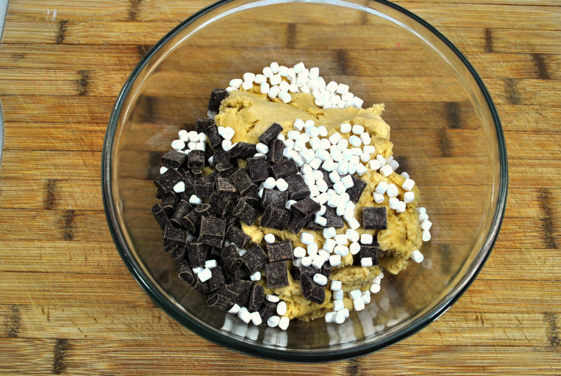 Glass bowl with cookie dough, mini marshmallows and chocolate chunks ready to be mixed.