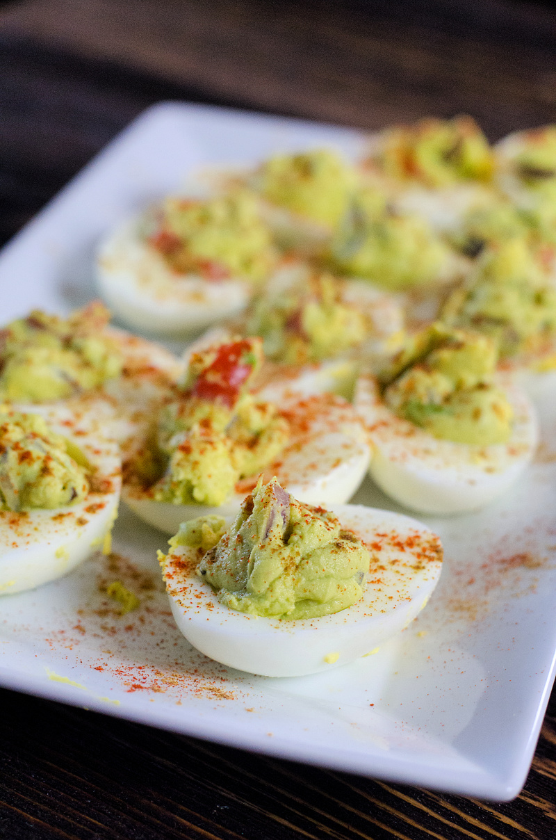 Guacamole deviled eggs on a plate paprika sprinkled on top