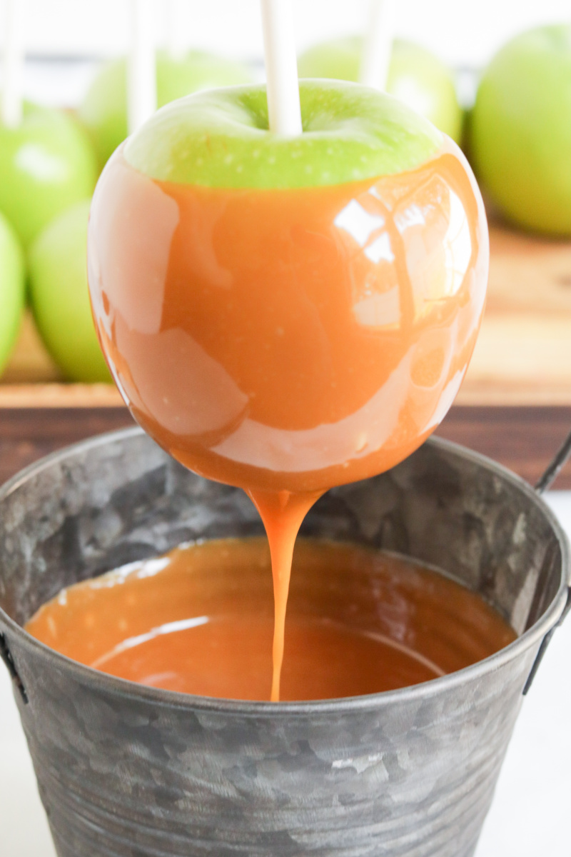 Apple being dipped in container of hot caramel sauce. Sauce is dripping form apple