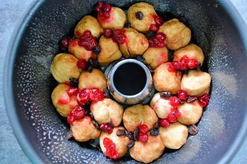 rolled dough balls with cranberry raisin mixture layered on top