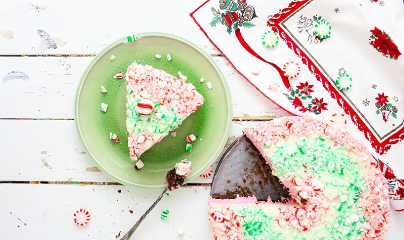 Beautiful no bake peppermint cheesecake slice on a green plate. Whole cheesecake is featured in the back with peppermint pieces sprinkled around the plate.