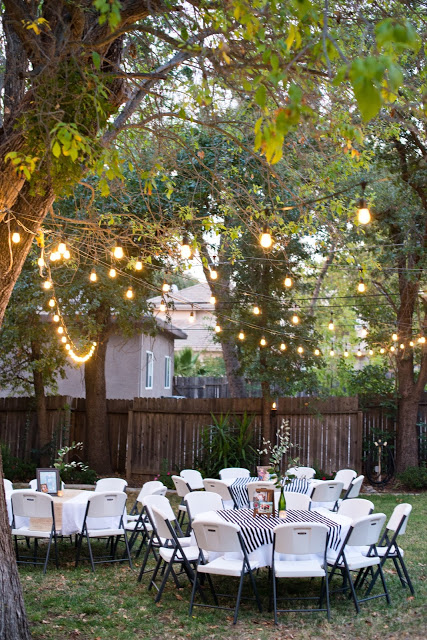 Backyard party lighting strung in the trees above tables