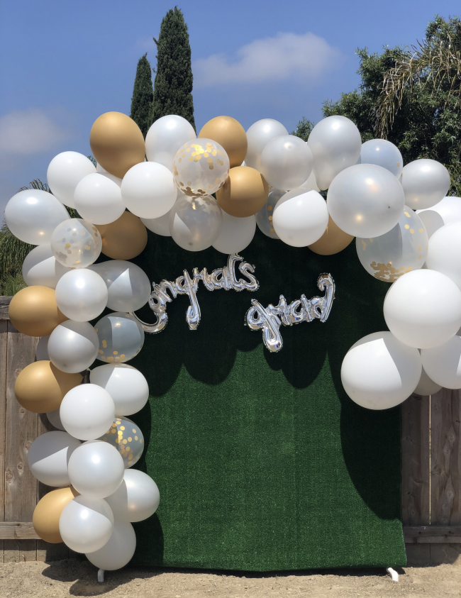 Green photo booth back drop with gold and white balloon garland. Congrats Grad silver balloon is attached to the backdrop.