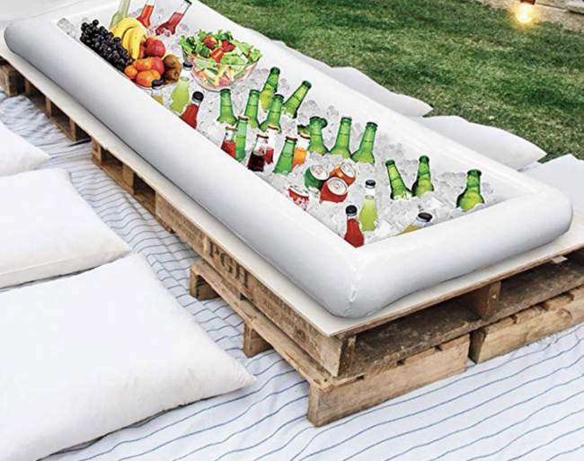 Rectangular inflatable bar sitting in the grass filled with drinks