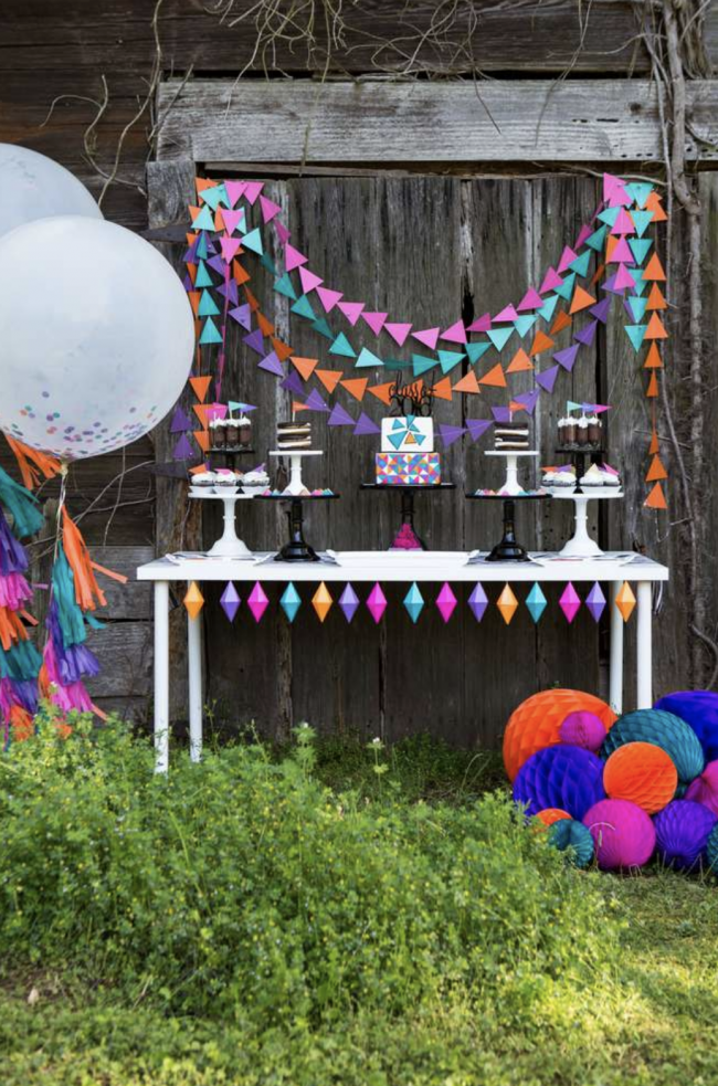 This outdoor graduation party dessert table is magical using bright colors, paper garlands and pretty cake plates to display the desserts. Consider adding large confetti balloons and paper spheres to accent the table.