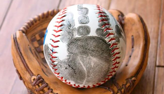 Classic white and red baseball with black handprint of small child