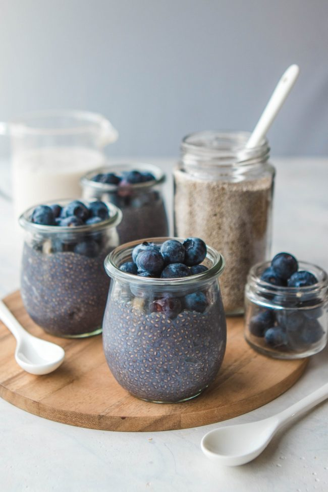 several blueberry chia puddings on a wooden serving plater.