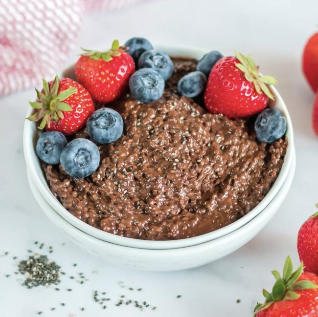 A bowl of yummy chocolate chia seed pudding topped with fresh blueberries and strawberries.