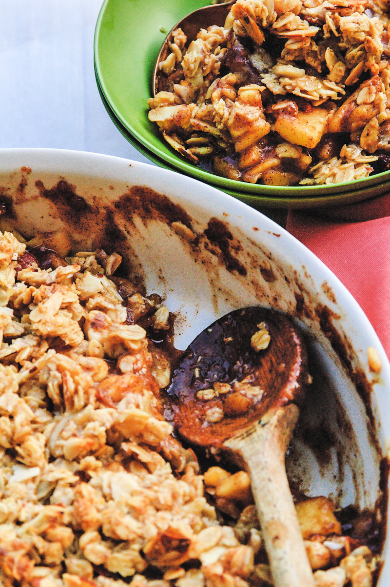 A delicious scoop of this apple crisp is served in a white dish adorn with a amber napkin.