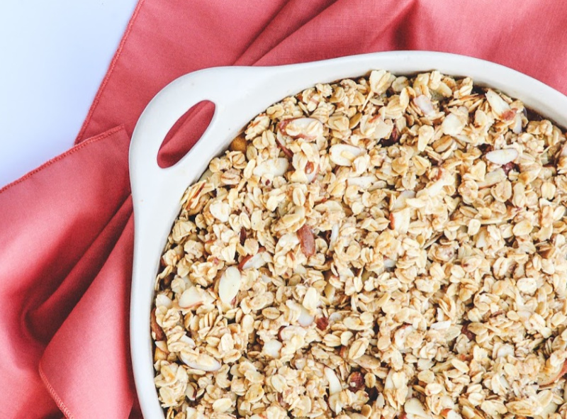 A closeup of this apple crisp is served in a white dish adorn with a amber napkin.