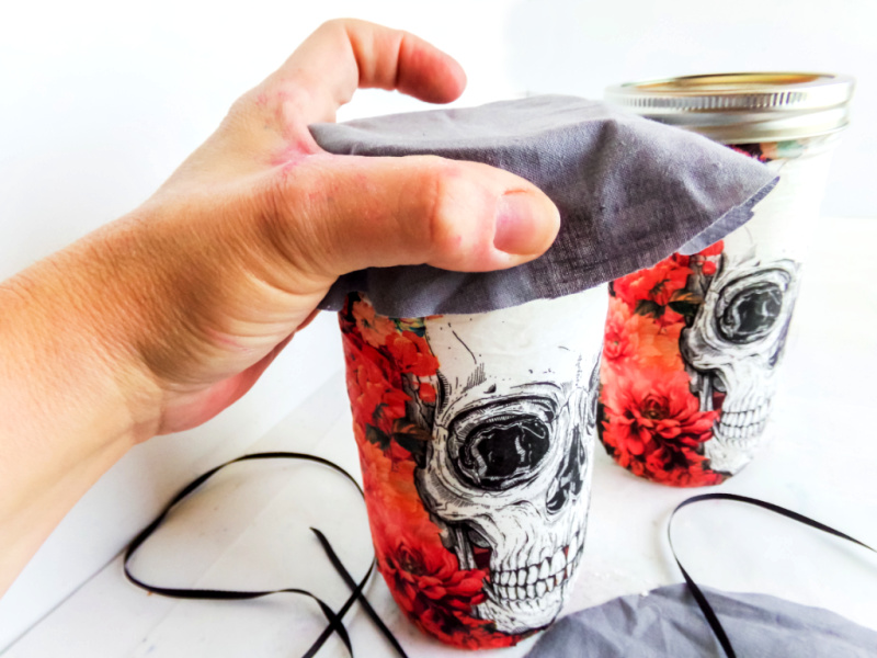 Place the piece of fabric on top of the jar and secure it in place with the string or raffia.
