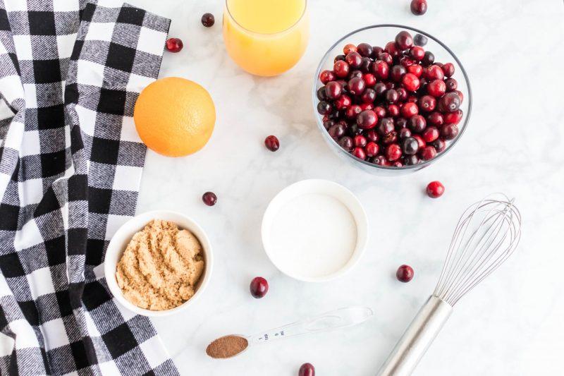 Individual bowls of cranberry sauce ingrediants including cranberries, orange juice and sugar.