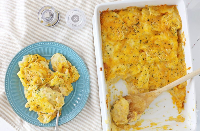 A serving of cheesy scalloped potatoes on a teal plate sitting along with the casserole dish on a beige and white napkin.