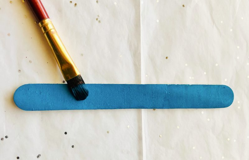 Paintbrush with teal paint painting a tongue depressor size popsicle stick.