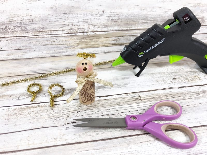 Cut a gold tinsel chenille stem in half with scissors. Wrap stem around your finger to create a circle, leaving a one inch long straight section, then twist to secure. Attach the angel's halo to the back of the wooden bead head.