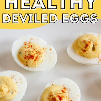 Deviled eggs sprinkled with paprika on a white plate.
