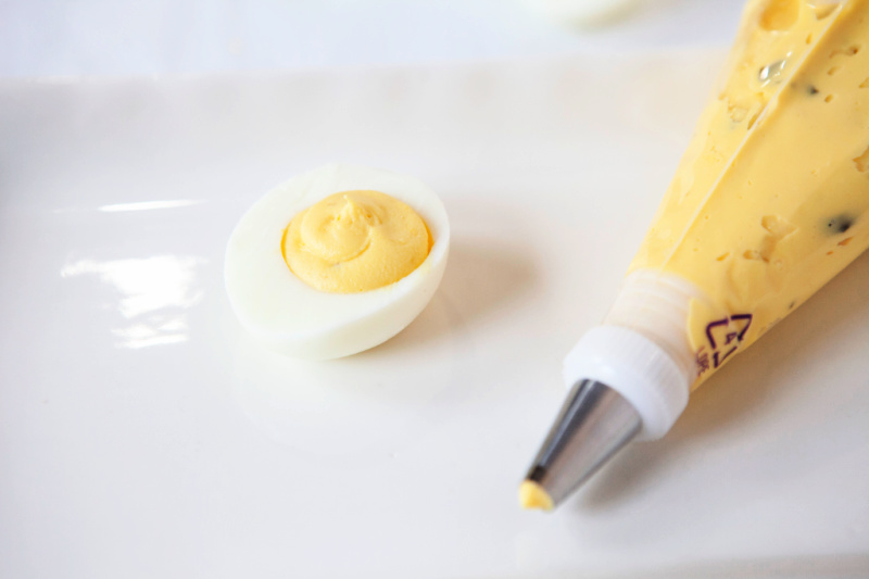 A filled egg white and a piping bag filled with blended egg yolks along side the egg.