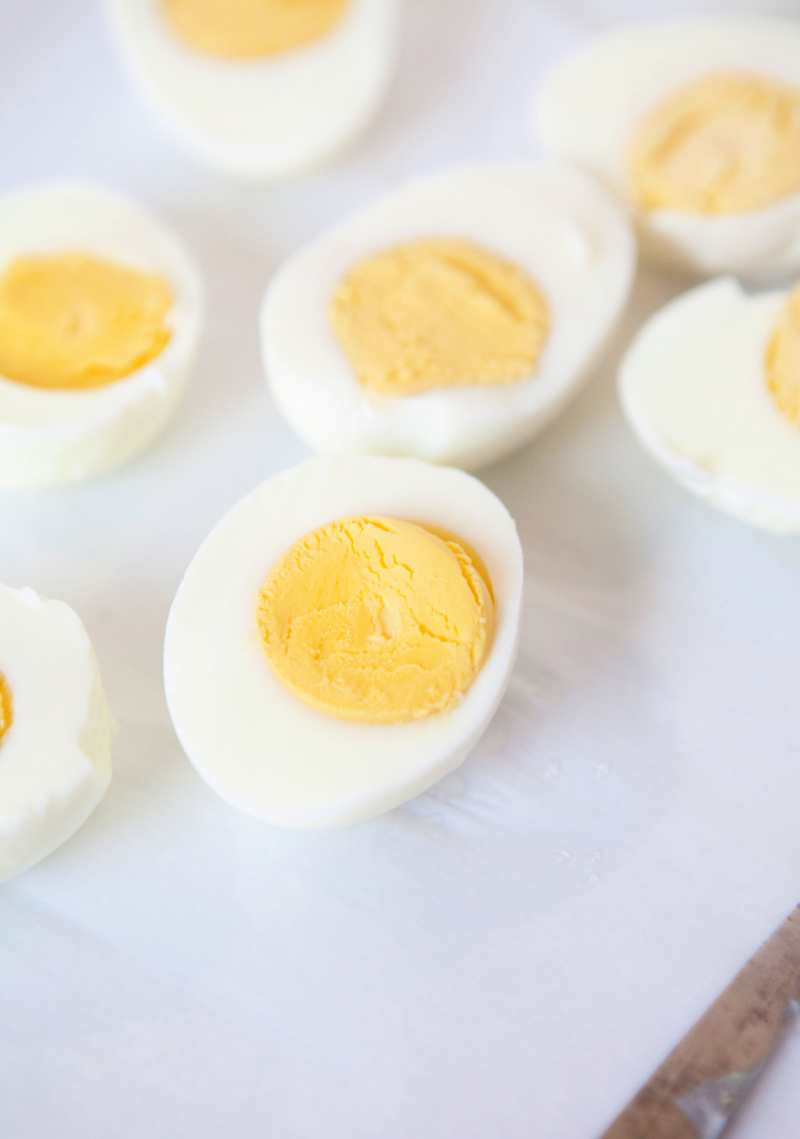 Hard boil eggs sliced in half on a white plate.