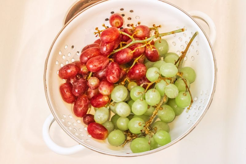 Washed red and green grapes in a white strainer.
