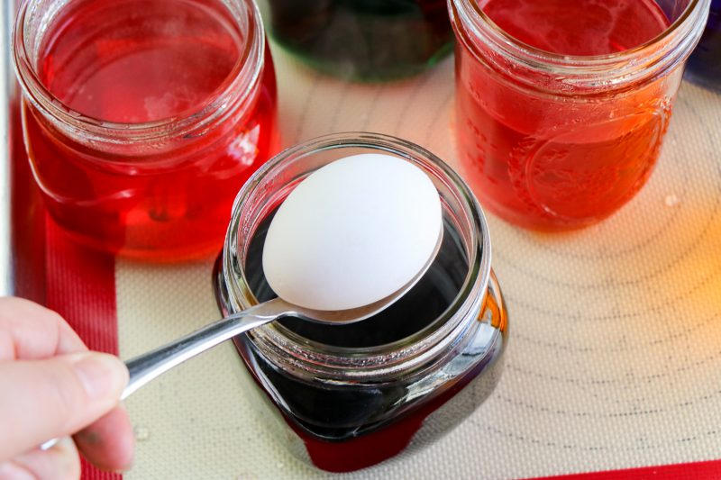 Using a spoon, lower a boiled egg into each container. Allow the eggs to sit for 5 minutes or more.