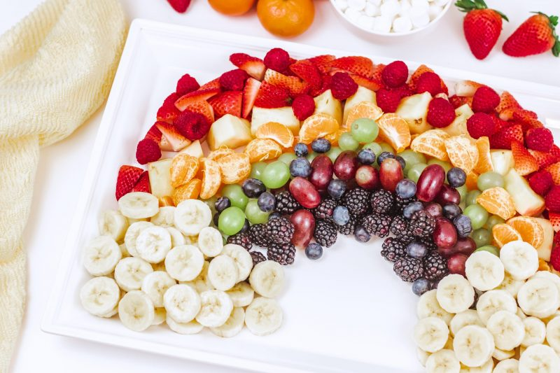 Rainbow fruit platter with bananas as the clouds. A bowl of marshmallows is also pictured as and option for clouds.