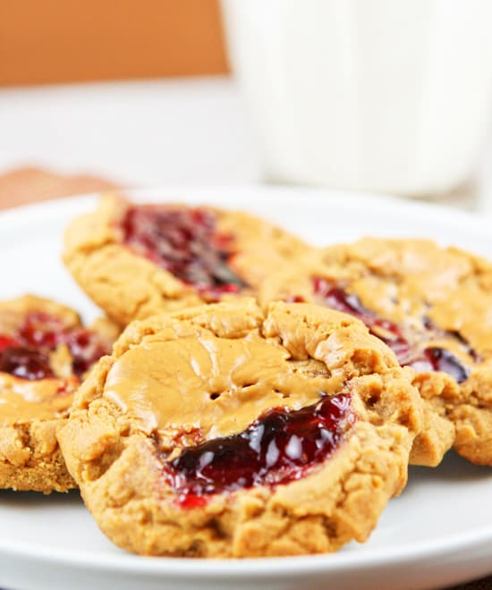 Round cookies made with a small indention in the top to add peanut butter and jelly