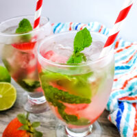 Strawberry mojito cocktail in a clear glass with a red and white paper straw. In the background is a red white and blue striped cloth napkin.
