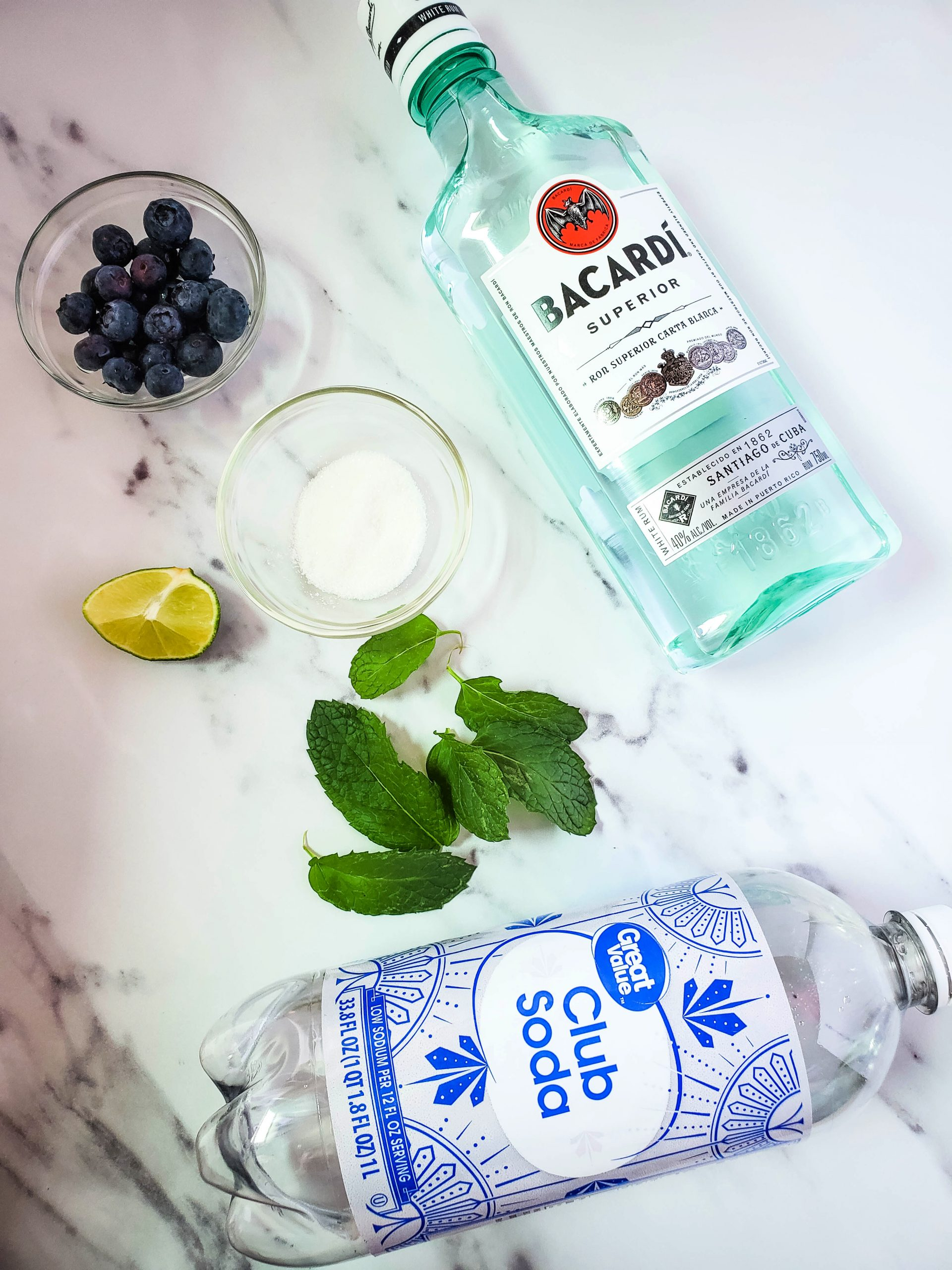 Blueberry Mojito ingredients - rum, club soda, blueberries and mint shown on a cutting board.