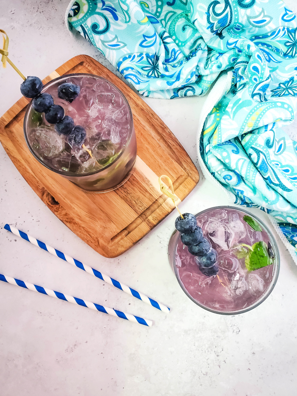 A blueberry mojito cocktail garnished with a skewer of blueberries and surrounded by a aqua hand towel and blue striped straws.