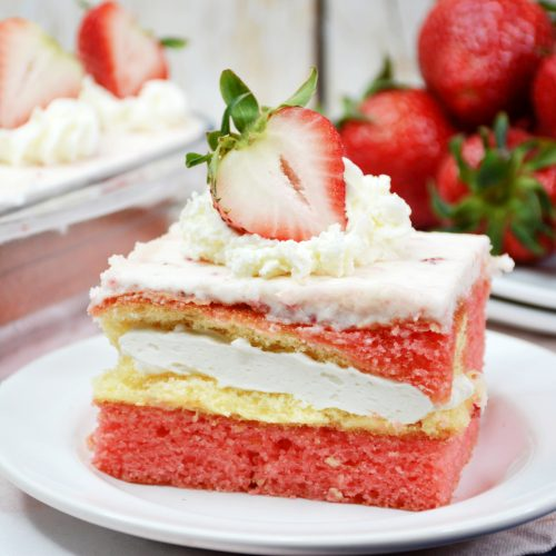 A square slice of strawberry Twinkie cake with homemade frosting and a slice of strawberry on top. The strawberry cake is sitting on a white dessert plate with a dish of strawberries in the background.