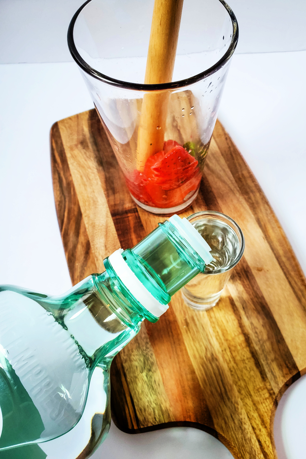 Strawberries and mint in a tall glass with a muddle sitting on a cutting board. Rum is being poured into a shot glass to add to the cocktail.
