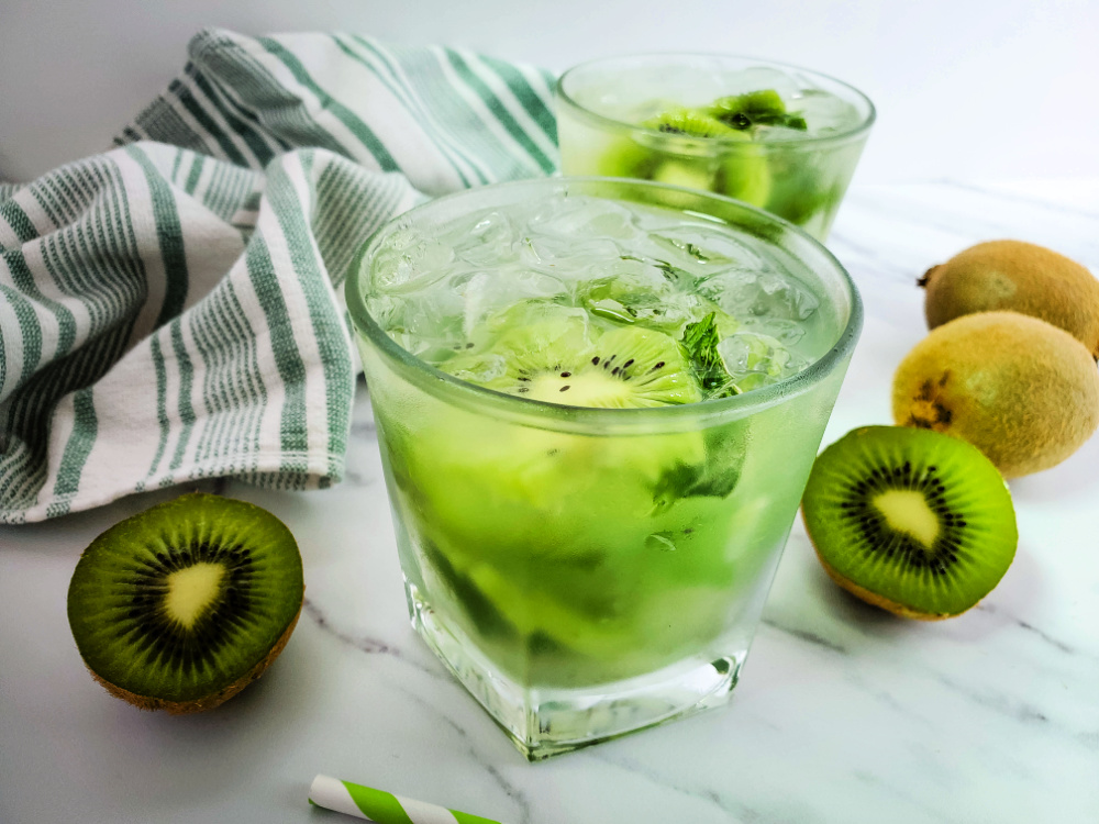 Kiwi mojito drink in a short cocktail glass with sliced kiwi, green and white cloth hand towel and a white marble background.