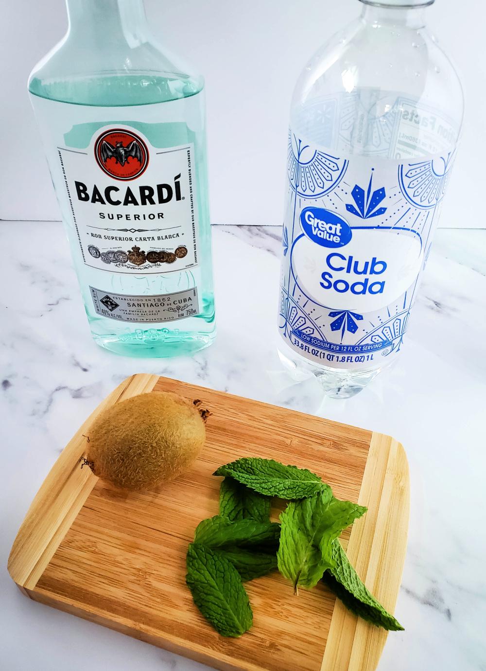 Kiwi Mojito ingrediants -  rum, club soda, kiwi and mint shown on a cutting board.