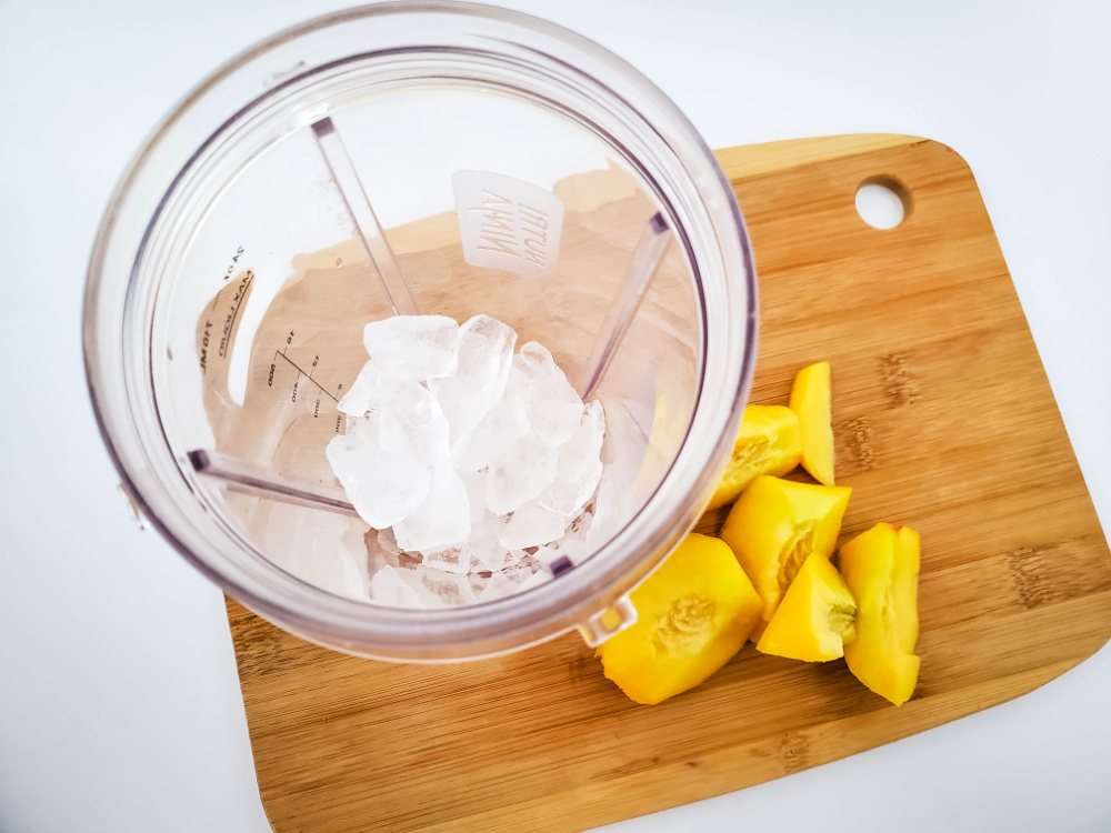 A blender with a cup of ice sitting on a cutting board with chopped peaches.